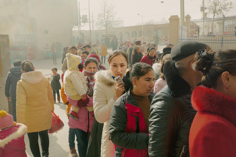 """3 février 2019. Hotan, Région autonome ouïghoure du Xinjiang, Chine. Des habitants ouïghours dans la file d'attente d'un point de contrôle d'identité et de fouille corporelle avant d'entrer dans le bazar de la ville. (Extrait de """"Dust"""" de Patrick Wack, éditions André Frère, 2021 / Copyright : Patrick Wack)"""