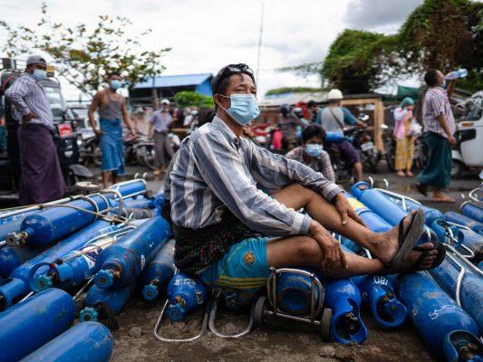 Un homme assis sur des bonbonnes d'oxygène vides dans l'attente de les remplir devant une usine à Mandalay, le 13 juillet 2021. (Source : Wowkeren)