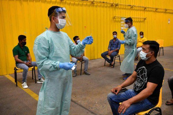Distribution d'autotests de dépistage du Covid-19 dans les dortoirs pour travailleurs immigrés à Singapour, le 13 septembre 2021. (Source : Nation Thailand)