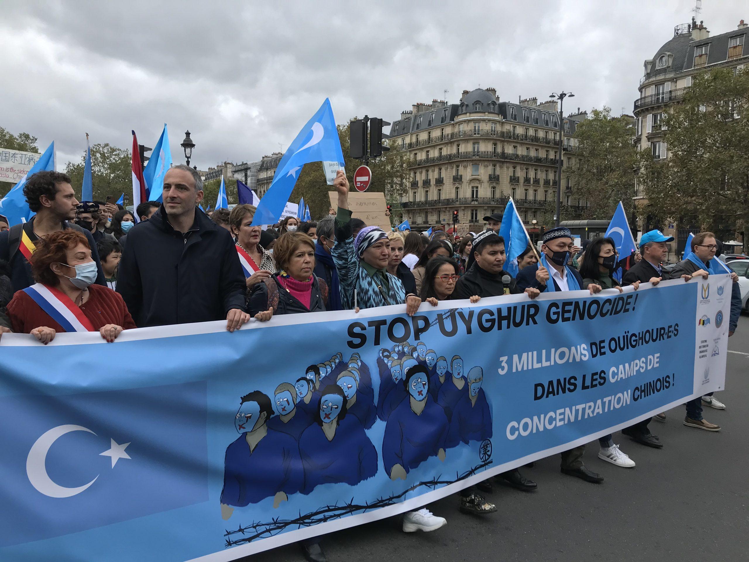 """L'eurodéputé Raphaël Glucksmann (2e à partir de la gauche) et Dilnur Reyhan, présidente de l'institut ouïghour européen (au centre), en tête de la """"marche contre le génocide ouïghour"""" organisé le 2 octobre 2021 à Paris. (Crédit : Baptiste Fallevoz)"""