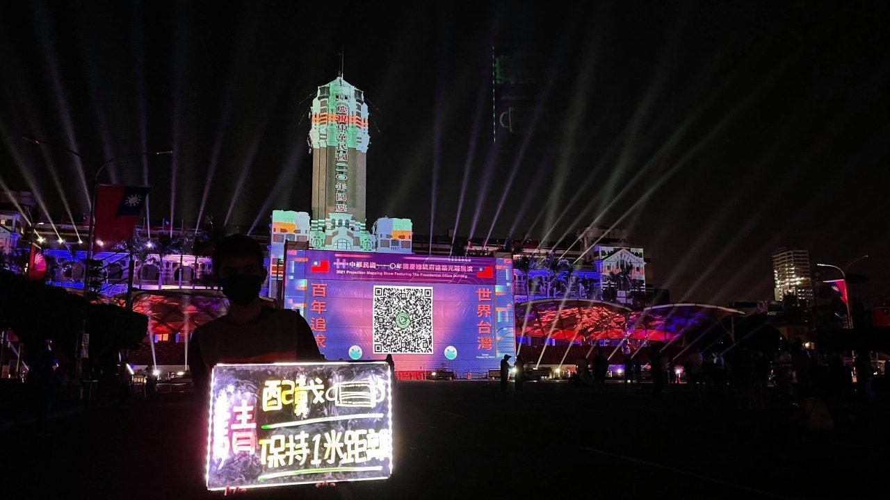 """Spectacle de lumière devant le plais présidentiel, la veille de la fête nationale à Taipei, le 9 octobre 2021. Un homme portant une pancarte luminescente rappelle vocalement et visuellement : """"Portez un masque, maintenez un mètre de distance."""" L'écran affiche le désormais célèbre QR code du Centre de control épidémique, scanné plusieurs fois par jour par tous les habitants de Taïwan afin de tracer les clusters, depuis que l'épidémie a touché l'île en mai 2021. (Copyright : William Han)"""